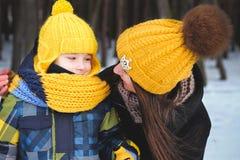 Fils d'annonce de mère en hiver photos stock