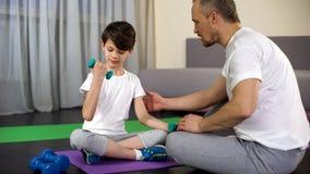 Fils d'enseignement de père pour faire des haltères s'exercer à la maison, enfance actif, soin image libre de droits