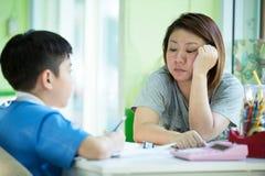 Fils de aide de mère asiatique sérieuse avec le travail Image libre de droits