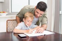 Fils de aide de père heureux avec le travail de maths à la table Photographie stock