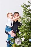 Fils de aide de papa pour décorer l'arbre de Noël images stock