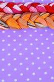 Fils de broderie de différentes couleurs sur un fond pourpre Photo stock