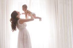 Fils de chéri de fixation de mère par les rideaux blancs Photographie stock libre de droits