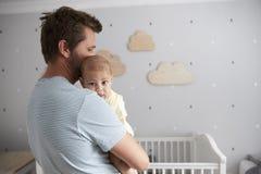Fils de Comforting Newborn Baby de père dans la crèche Photographie stock libre de droits