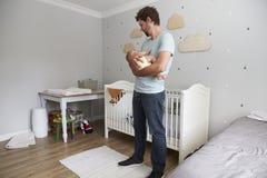 Fils de Comforting Newborn Baby de père dans la crèche Photos libres de droits