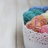 Fils de coton multicolores dans le panier sur le fond en bois blanc Images stock