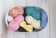 Fils de coton multicolores dans le panier sur le fond en bois blanc Photo stock