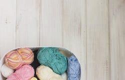 Fils de coton multicolores dans le panier sur le fond en bois blanc Photographie stock