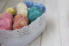 Fils de coton multicolores dans le panier sur le fond en bois blanc Photos stock