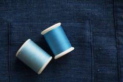 Fils de couture bleus de ton sur le fond bleu de tissu Images stock