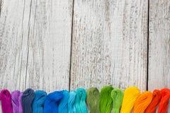 Fils de couture colorés pour la broderie sur le fond blanc Image stock