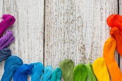 Fils de couture colorés pour la broderie sur le fond blanc Images stock