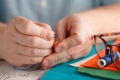 Fils de couture colorés sur des bobines avec l'aiguille Photo libre de droits