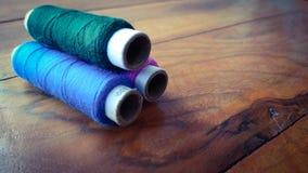 Fils de couture colorés sur le fond en bois Photos stock