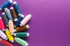 Fils de couture colorés sur le fond violet Photos libres de droits