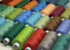 Fils de couture dans différentes couleurs de bobines Image stock