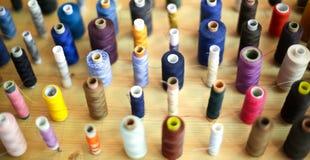 Fils de couture disposés sur le conseil en bois Photographie stock