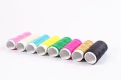 Fils de couture multicolores sur le fond blanc, Image stock