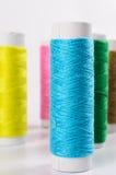 Fils de couture multicolores sur le fond blanc, Photographie stock libre de droits