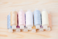 Fils de couture multicolores sur le fond en bois Photo stock