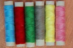 Fils de couture multicolores sur le plan rapproché de toile de fond Photos libres de droits