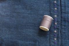 Fils de couture roses foncés sur le fond bleu de tissu Photo libre de droits