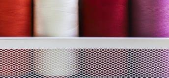 Fils de couture sur la bobine dans la boîte de grille en métal blanc Photos libres de droits