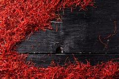 Fils de crocus de safran sur le fond en bois noir Photographie stock libre de droits