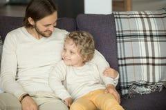 Fils de embrassement d'enfant de père heureux s'asseyant sur le sofa à la maison Photographie stock