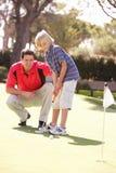 Fils de enseignement de père pour jouer au golf Photographie stock