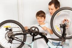 Fils de enseignement de papa réparant la bicyclette utilisant la clé Photos libres de droits