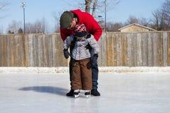 Fils de enseignement de père comment au patin de glace Image libre de droits