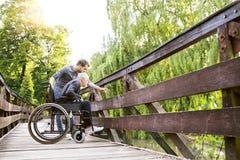 Fils de hippie marchant avec le père handicapé dans le fauteuil roulant au parc Images libres de droits