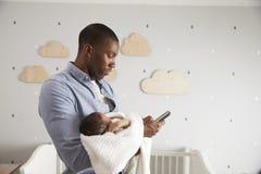 Fils de Holding Newborn Baby de père à l'aide du téléphone portable Photographie stock