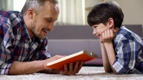Fils de lecture de papa excitant le livre d'imagination, l'imagination et la créativité, temps libre image libre de droits
