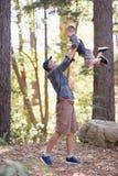 Fils de levage de père tout en augmentant dans la forêt Image libre de droits