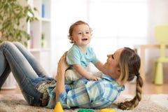 Fils de mère et de bébé ayant un amusement sur le plancher à la maison Femme et enfant détendant ensemble Photographie stock libre de droits