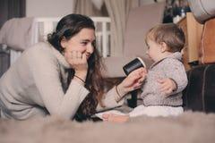 Fils de mère et de bébé jouant ensemble à la maison Bébé de enseignement à boire de la tasse Style de vie heureux de famille Images libres de droits
