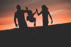 Fils de oscillation de mère et de père dans le ciel au coucher du soleil Image libre de droits