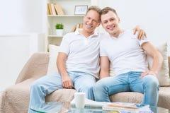 Fils de père et d'adulte s'asseyant sur le sofa Photos stock