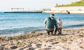 Fils de papa et d'enfant en bas âge sur la plage Photo stock