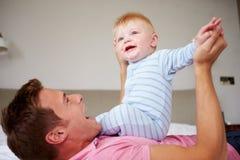 Fils de Playing With Baby de père comme ils se situent dans le lit ensemble Photo stock