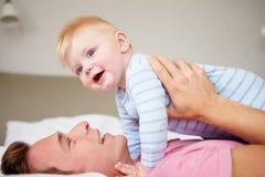 Fils de Playing With Baby de père comme ils se situent dans le lit ensemble Photographie stock