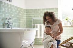 Fils de séchage de mère avec la serviette après Bath Photo libre de droits