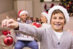 Fils de sourire tenant la babiole devant sa famille Photographie stock libre de droits