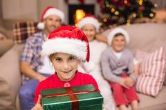 Fils de sourire tenant le cadeau devant sa famille Image stock