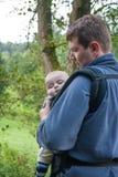 Fils de transport de jeune père dans l'élingue dans la forêt d'été photos libres de droits