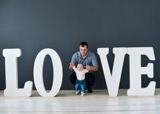 Fils de transport de père heureux d'isolement sur le fond gris près de grandes lettres de l'amour de mot Photographie stock