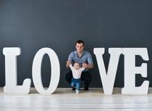 Fils de transport de père heureux d'isolement sur le fond gris près de grandes lettres de l'amour de mot Image stock