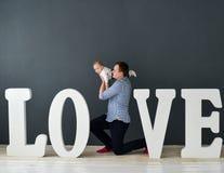 Fils de transport de père heureux d'isolement sur le fond gris près de grandes lettres de l'amour de mot Image libre de droits